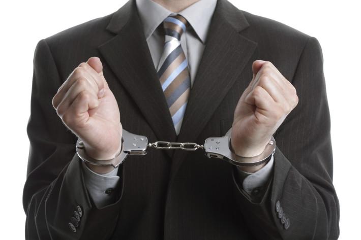 Corporate crime concept, businessman wearing handcuffs