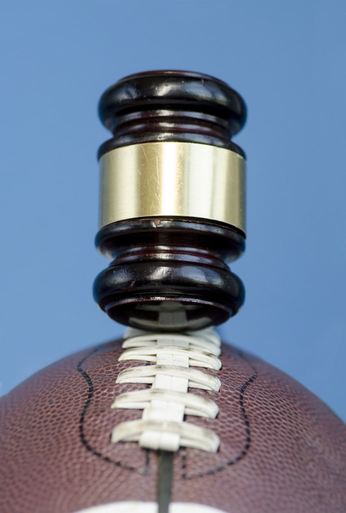 Football with gavel, legal issues connected with the sport concept issue.