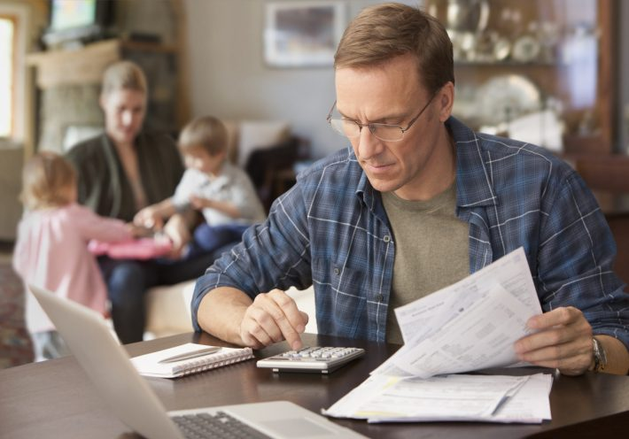 Man-Working-Out-Finances-iStock-137925642-710x496