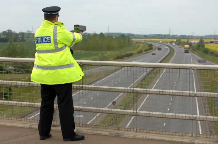 A British Police officer operating a hand held speed gun
