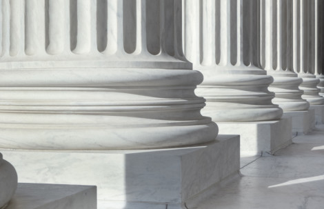 An image of architectural detail from the United States Supreme Court building.  There are circular pillars visible in a row.  The pillars are white.  Each pillar has a block at the bottom, followed by three circular lines going all around them.  Vertical lines come next in an alternating pattern of sunken lines and protruding ones.  There are six pillars visible in the image, but only their lower parts can be seen.  The floor has white tiles.  There is sunlight coming from the front of the building, creating shadows behind the pillars.