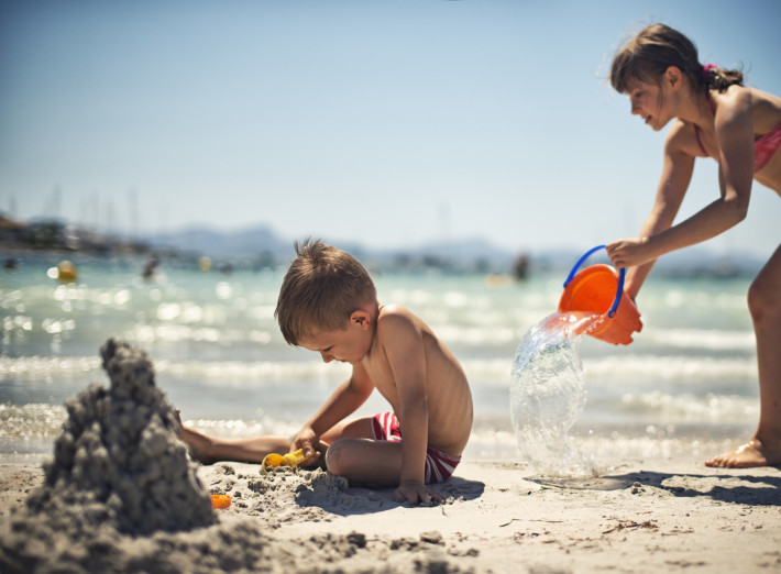 Little boy is playing on a beach while his sister has sneaked behind hims with a bucket of water and is just pouring the water on him.