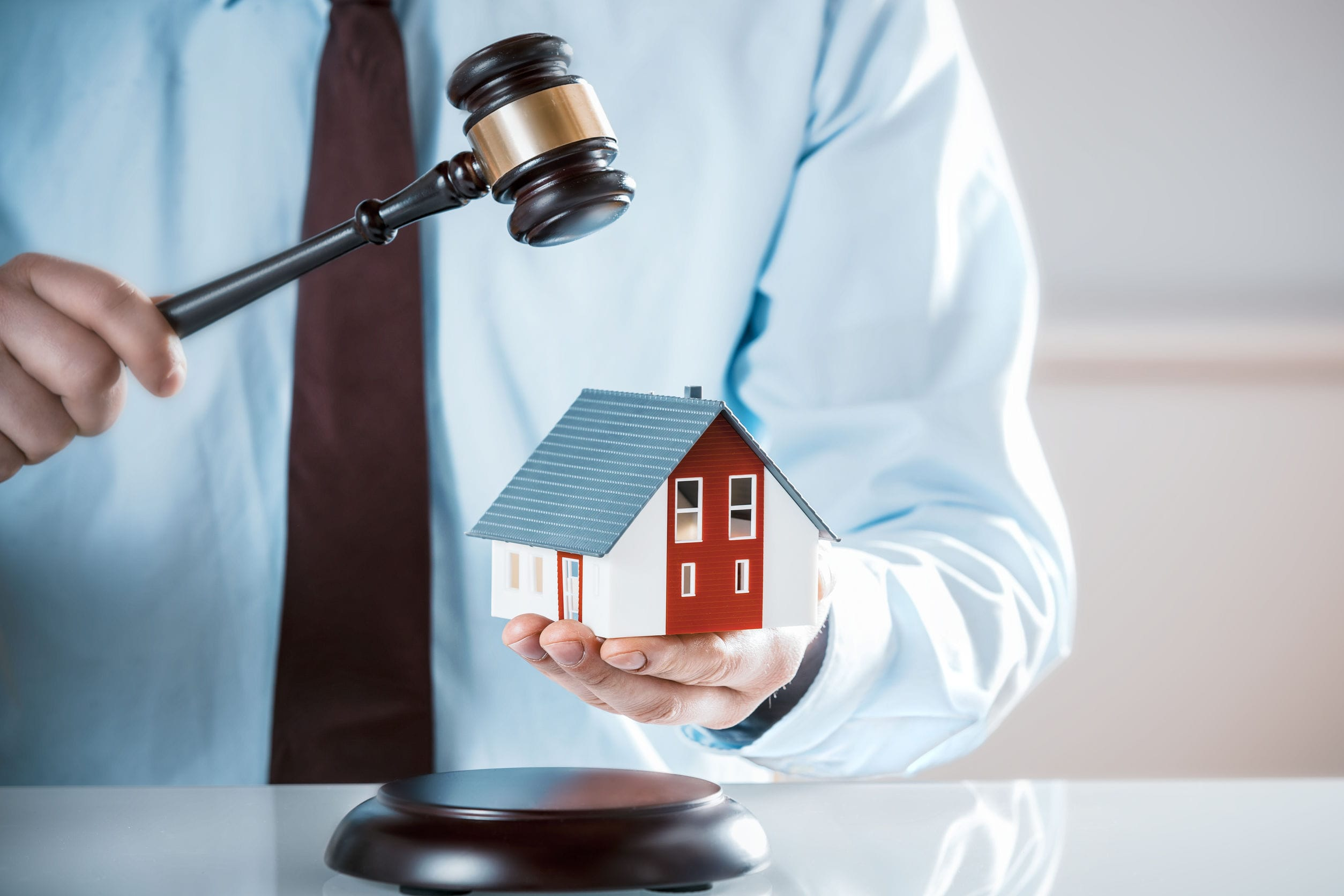 Auctioneer knocking down a property sale holding a model house as he raises his gavel, or a lawyer or judge mediating in a property dispute in court